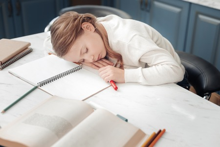 Want to sleep. Cheerful schoolgirl sitting at her workplace and leaning on her arms Stock Photo