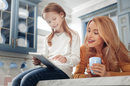 So delighted. Beautiful girl sitting on table while demonstrating her gadget to mom