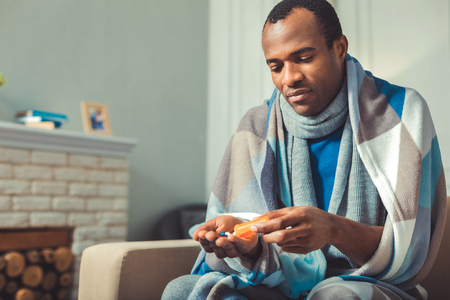 Bad health. Unhappy afro american man taking pills and sitting Stock Photo