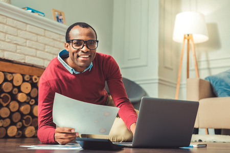 Working process. Positive afro american man looking at camera and using laptop