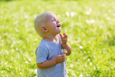 Funny moments. Smiling happy kid laughing while having fun in the garden