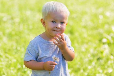 Funny games. Shy sweet kid having fun while spending time in the garden Stock Photo