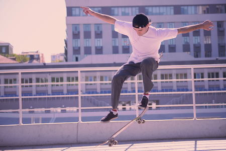 Just do it. Serious male person raising arms while testing new skateboard