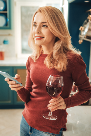 So dreamy. Beautiful woman holding glass bocal with wine and looking aside Stock Photo