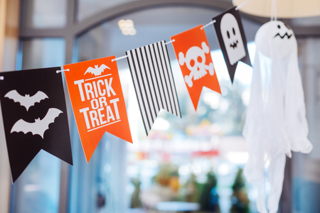 Funny and scary. Cute funny and scary little flags with skulls and bats hanging above Halloween table for children party Stock Photo