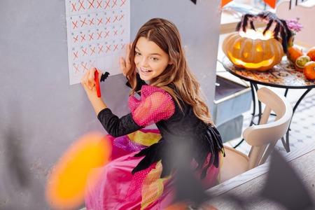 Wall calendar. Funny fashionable girl wearing pink and black Halloween dress standing near her wall calendar