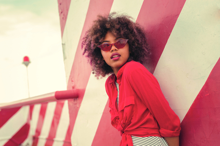 Attractive young girl. Beautiful curly young woman wearing red glasses with red clothes and looking into the distance