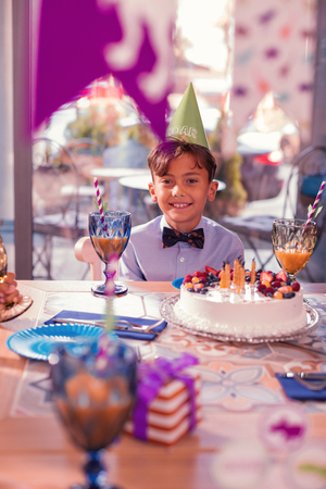 Relaxed boy. Positive relaxed boy wearing party hat and smiling while sitting at the table with big cake in front of him