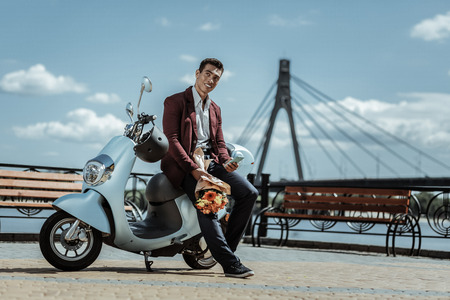 Romantic date. Low angle of handsome glad guy holding bouquet of flowers and leaning on motorbike Stock Photo