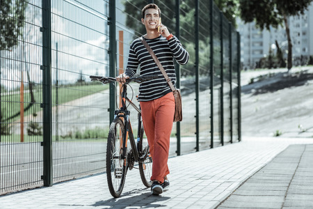 Close to you. Optimistic jovial guy leaning on bicycle and talking on phone