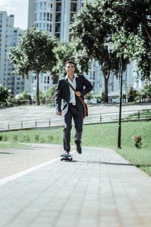 Active lifestyle. Low angle of happy male student riding on skateboard and clothing in suit