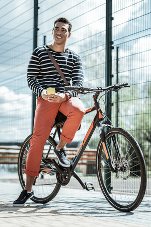 Healthy lifestyle. Low angle of handsome cheerful guy sitting on bicycle and carrying phone