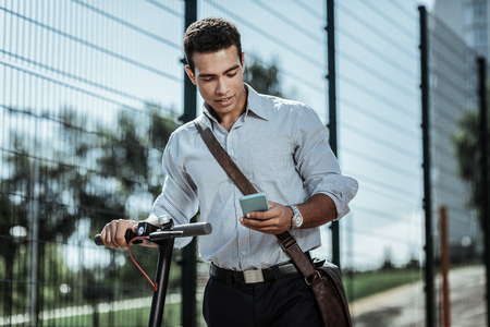 Special app. Attentive calm guy launching app for riding electric scooter