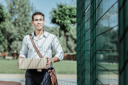 International delivery. Low angle of appealing male courier holding package and wearing suit Фото со стока