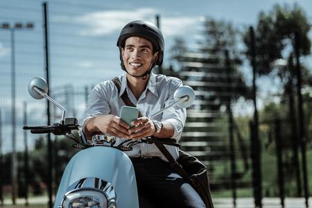 Think once again. Low angle of joyful glad guy posing on motorbike and gazing aside