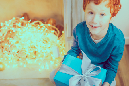 Look at me. Joyful boy raising head while looking upwards and holding present