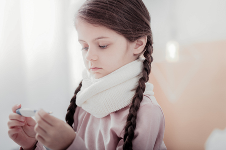 Infection. Close up of pale little girl holding thermometer in hands while looking at it with sadness in her eyes