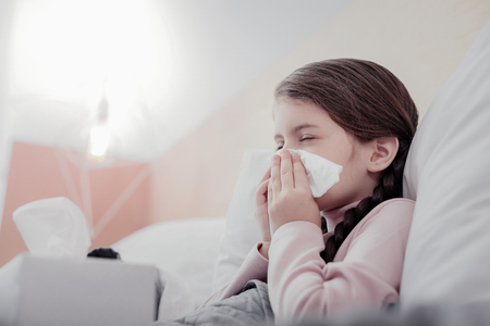 Unpleasant condition. Close up of small pale girl using napkins while keeping her eyes closed and sneezing Stock fotó