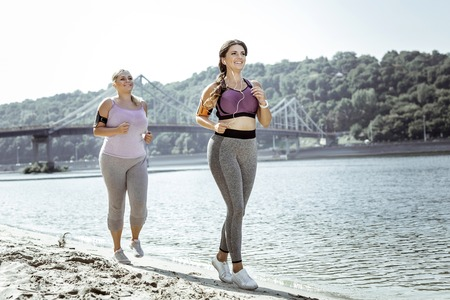 Sports workout. Delighted nice women jogging near the river while having cardio training