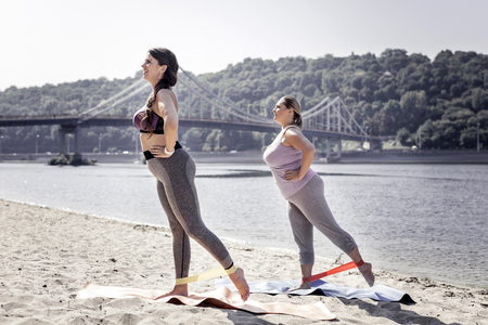 Synchronous movements. Nice young women standing on yoga mats while doing an exercise together Stockfoto