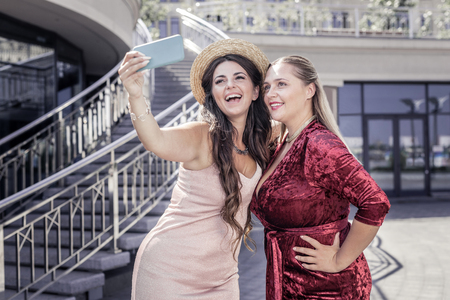 Happy sisters. Delighted happy women standing together while taking a selfie