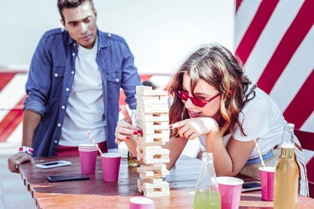 Be careful. Charming female expressing positivity while playing table game in group of her friends Stock Photo