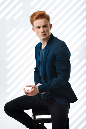 Very stylish. Charming pretty guy sitting on chair and touching jacket Stock Photo
