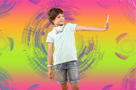 Perfect focus. Confident charming boy taking selfie and posing on colorful background