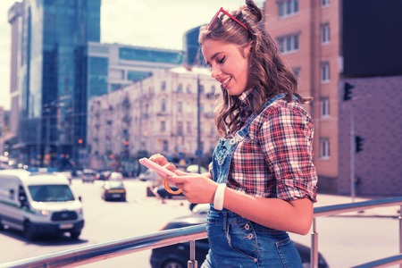Modern girl. Modern beaming girl wearing white smart watch reading her electronic book while standing outside