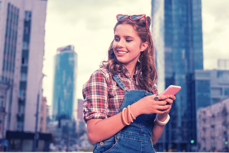 Message for boyfriend. Curly appealing smiling student holding her pink phone while writing message her boyfriend
