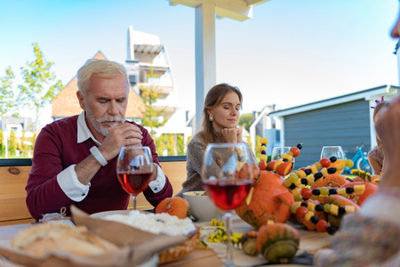 Pray for family. Kind male person leaning elbow on table while preparing emotionally for dinner