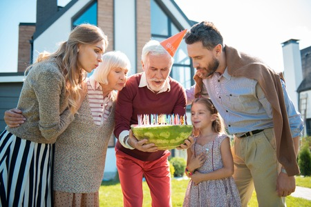 Birthday cake. Concentrated mature man bowing head while making wish Stock Photo