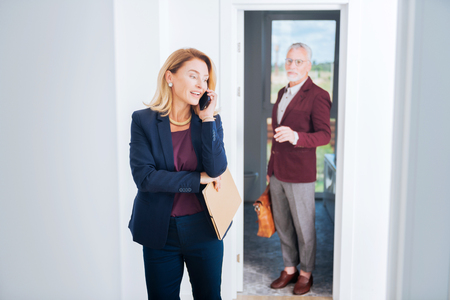 Speaking with client. Blonde-haired real estate broker wearing elegant blue costume speaking by phone with her prosperous client Banco de Imagens