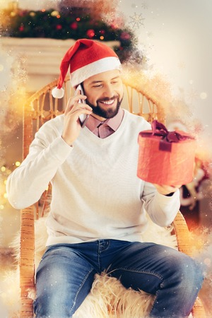 Inviting for dinner. Bearded handsome man calling his girlfriend inviting her for Christmas dinner while having gift for her