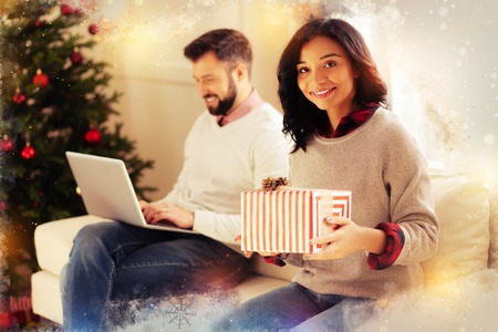 Gift box. Appealing pleasant beaming wife wearing grey sweater holding nice red Christmas gift box from her husband