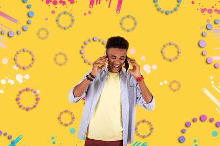 Two phones. Funny mulatto teenager depicting near colorful background laughing out loud while speaking by two phones at a time Stock Photo