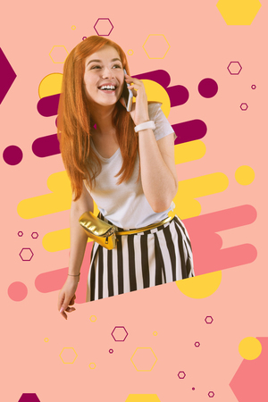 Red-haired girl. Funny red-haired girl using her new smartphone standing ahead of bight pink and yellow graphic ground