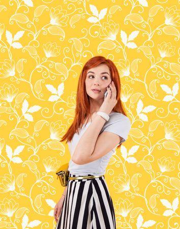 Interesting information. Young attractive girl looking curious while standing against the flower patterned background and having a pleasant phone conversation Stock Photo