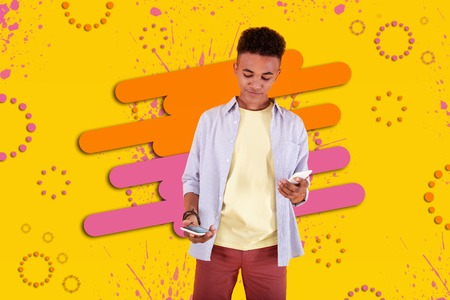 Fond of technology. Modern dark-haired boy being in front of graphic ground fond of technology holding two electronic devices in his hand Stock Photo