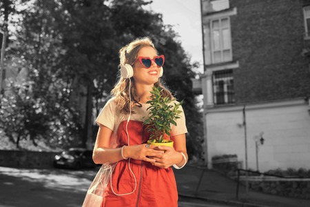 Beaming girl. Beaming girl listening to music in her white earphones feeling truly relaxed while going home with plant
