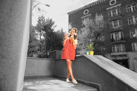 Music and juice. Student standing near her house listening to music in her white earphones and drinking orange juice Stock Photo