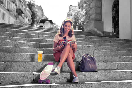 Revising material. Modern beautiful diligent student sitting on the stairs outside the university revising material