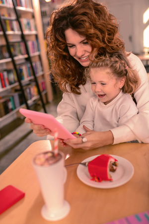 Funny joke. Positive delighted female person embracing her kid while holding tablet in both hands
