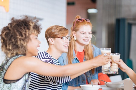 Milk cocktail. Charming red haired girl expressing positivity while communicating with her friends Banque d'images