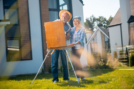 Straw hat. Bearded smiling man wearing straw hat helping his talented wife drawing nature near their house