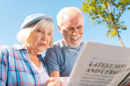 Seeing story. Grandmother and grandfather feeling happy seeing story about their grandchildren in newspaper Stock Photo