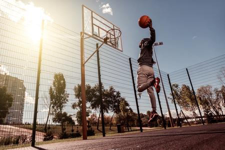 Perfecte slag. Knappe Afro-Amerikaanse man die een bal vasthoudt terwijl hij hem in de basket gooit