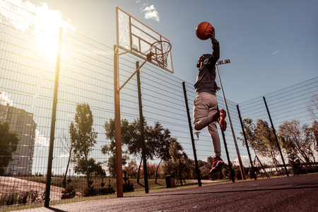 Perfect hit. Handsome Afro American man holding a ball while throwing it into the basket