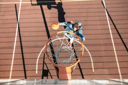 Interesting game. Top view of a nice young man playing basketball while being on the sportsground