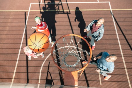 This is a score. Top view of a ball flying into the basket while playing a basketball game